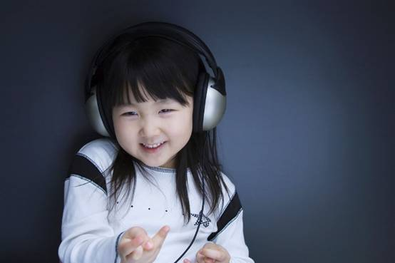 Little girl listening to music through headphones.