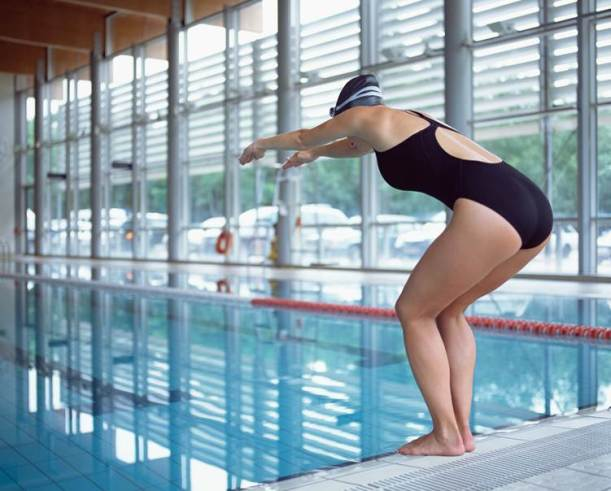 A woman standing at the edge of a pool about to dive in.