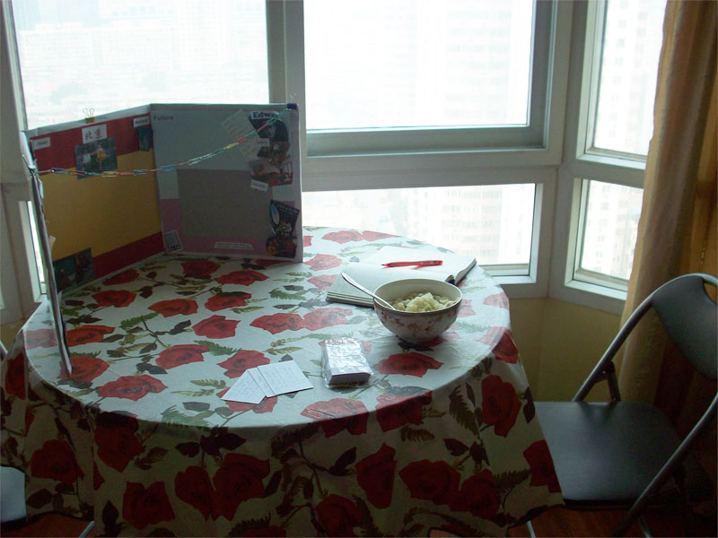 A foldout table and chair, with my visionboard, my notebook and my lunch bowl.