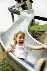 A little girl squealing as she shoots down a metal slide.