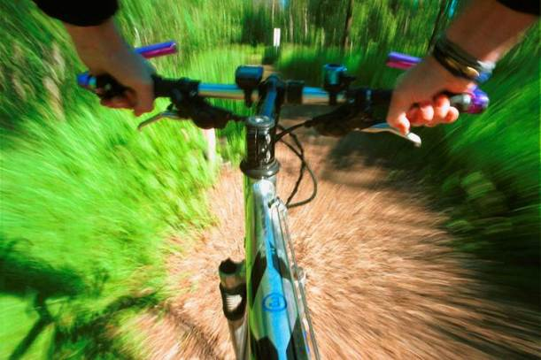 The front of a mountain bike heading down a dirt path at speed