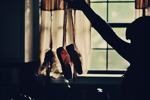 A girl holding up ballet shoes.