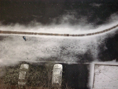 An aerial view of a man walking in the snow.