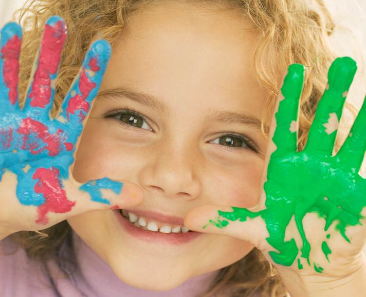 A little girl with paint all over her hands, looking very pleased with herself