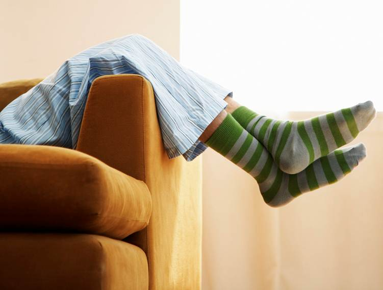 A person relaxing on a couch in pyjamas and green stripy socks
