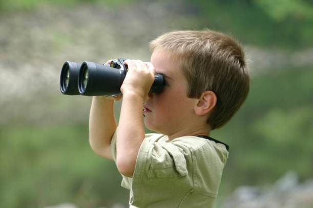 A little boy with binoculars looking into the distance