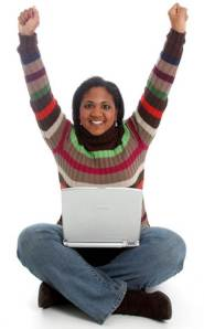 A woman with a computer on her lap and her hands in the air