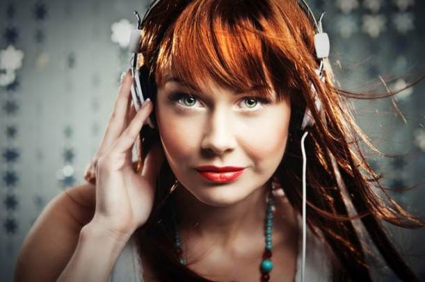 Redheaded girl listening to music through headphones