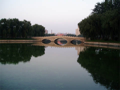 A bridge over a lake in a park somewhere in Beijing