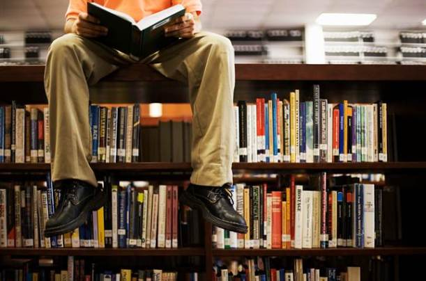Man sitting on a bookcase
