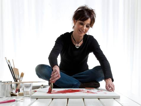 A woman sitting on a table, painting a canvas with creative abandon.