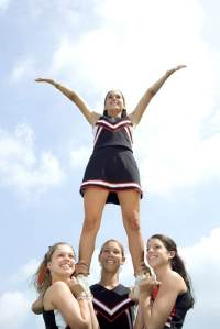 Three cheerleaders holding a fourth girl on their shoulders
