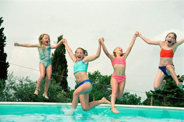 Four kids jumping into a pool holding hands