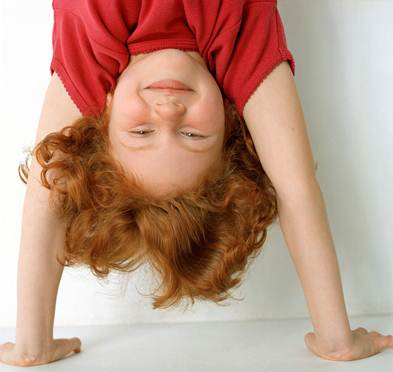 A red-haired girl doing a handstand