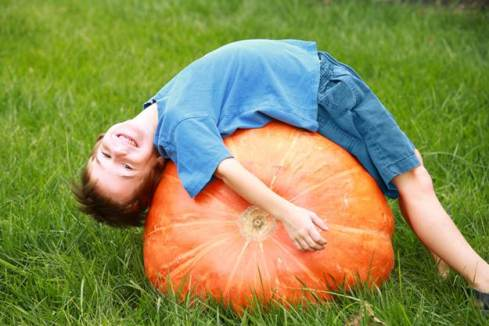 A boy lying on a pumpkin...or should that be 'lying over a pumpkin'?