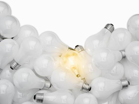 A pile of light bulbs with one bulb lit up, causing the viewer to wonder if light is contagious.