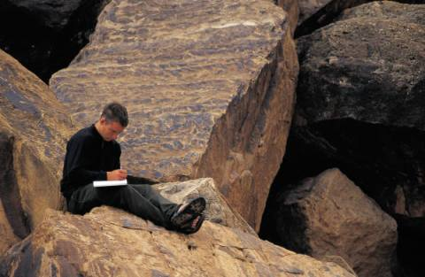A man writing while sitting atop a rock. I hope he doesn't drop his pen.