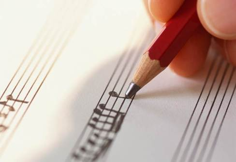 A hand writing music. (I presume the hand is attached to an off-screen body, otherwise the image would be down-right creapy)