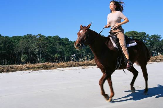 A woman riding her horse along a beach.