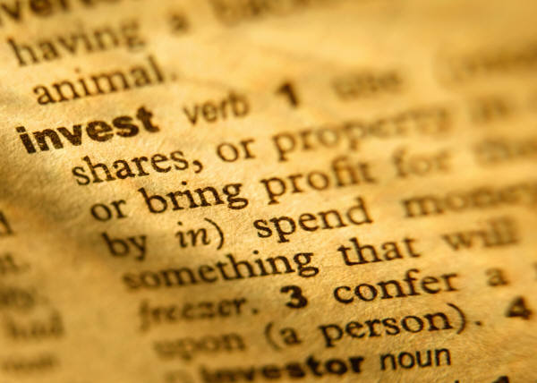 A dictionary opened to the word 'invest.'